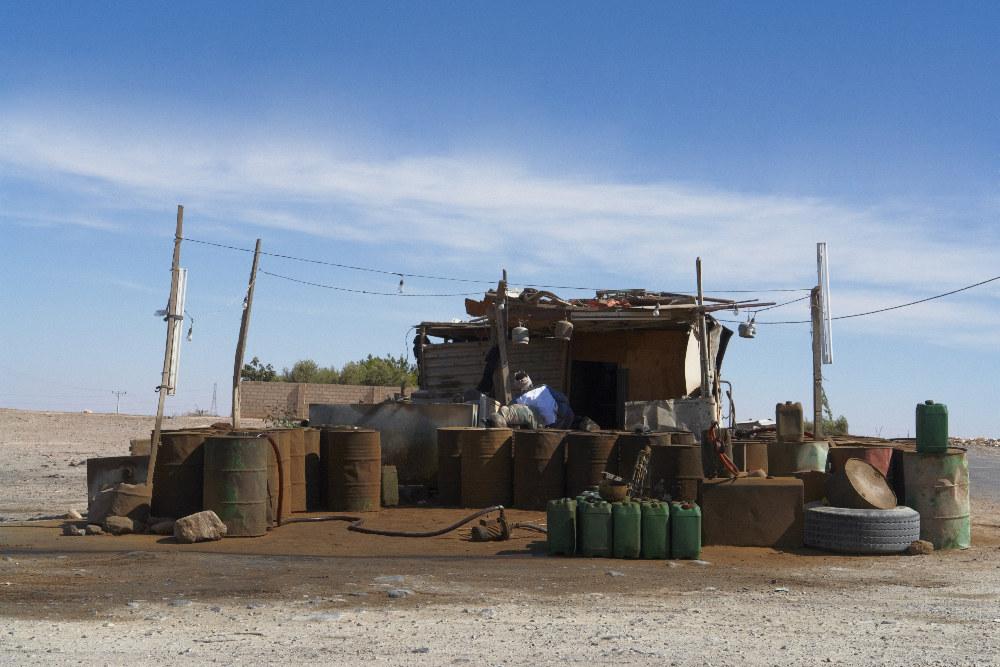 Jordanien, eine kleine Straße abseits des King Desert Highway. Die Sonne brennt unbarmherzig, es ist kurz nach Mittag. Was nicht unbedingt draußen sein muß, sucht Unterschlupf - Stilleben. Schon von weitem ist die Tankstelle olfaktorisch auszumachen, es riecht markant nach Diesel. Unter dem Vordach seiner spärlichen Behausung sucht der Tankwart Schutz vor der Hitze und lässt sich auch nicht beirren, als ich stehen bleibe. Während man an den modernen Tankstellen des Highway eiskalte Getränke aus dem Kühlschrank bekommt, findet sich hier Gastfreundschaft in Form von Tee und einer - wenn auch aufgrund der Sprachbarriere - holprigen Unterhaltung. Er sagt: 'Welcome in Jordania' - ich denke, als ich die Szene in mich aufnehme: 'Welcome into my soul'.